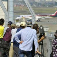 Aircraft enthusiasts gaze at a Mitsubishi Regional Jet from the observation deck at Nagoya Airport in October. | KYODO