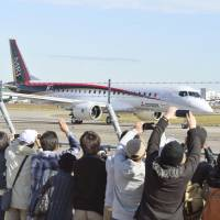 People watch the Mitsubishi Regional Jet, the country's first homegrown passenger plane in half a century, take off on its maiden flight from Nagoya airport in Aichi Prefecture on Wednesday. | KYODO