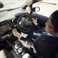 Nissan Motor Co. General Manager Tetsuya Iijima takes his hands off of the steering wheel of a self-driving prototype vehicle during a test drive in Tokyo on Tuesday. Prime Minister Shinzo Abe will ease regulations to allow self-driving cars to be tested on public roads. | AP