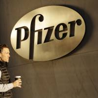 A man enters Pfizer's world headquarters Monday in New York. Pfizer and Allergan will join in a $160 billion deal to create the world's largest drugmaker. | AP