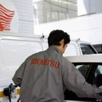 An attendant polishes a car at an Idemitsu Kosan Co. gas station in Tokyo. The refiner agreed to merge with Showa Shell Sekiyu K.K. amid lower fuel demand.   BLOOMBERG