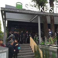 Eager customers form a line in front of New York-based hamburger restaurant chain Shake Shack before it opened its first Japanese outlet in Tokyo's Meiji Jingu Gaien park on Friday. | KAZUAKI NAGATA