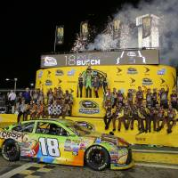 Kyle Busch raises his trophy after winning the NASCAR Sprint Cup Series auto race and the season title Sunday at Homestead-Miami Speedway in Homestead, Florida. | AP
