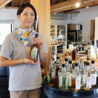 Cheers: An employee stands in front of the wares on offer at Venture Whisky.   KYODO