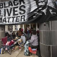 Black Lives Matter members sit in the lobby of the Minneapolis Police Department's fourth precinct headquarters with residents of north Minneapolis on Monday. | AP
