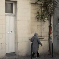 A woman walks by the house of the family of Belgian militant Abdelhamid Abaaoud in Molenbeek, Belgium, on Wednesday. The family homes of the suspected mastermind of the Paris attacks and one of the suicide bombers stand only a few blocks apart in the Belgian capital's Molenbeek neighborhood.   AP