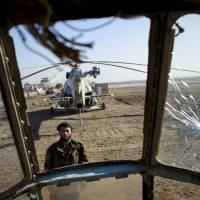 A soldier of the Afghan National Army is seen through the cockpit of a scrapped Russian helicopter as he guards Kunduz airport in this file photo from 2011. Some people within NATO are questioning the wisdom of sinking further resources into the 12-year mission as fatigue and frustration exact a toll. | REUTERS