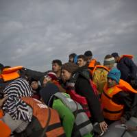 Refugees from Syria and Iraq arrive on a dinghy from the Turkish coast to the Greek island of Lesbos, Tuesday. Several European countries, including EU members Slovenia and Croatia and nonmembers Serbia and Macedonia, have declared they will only allow 'war-zone refugees' from Afghanistan, Iraq and Syria to transit through their countries on their way to Central and Northern Europe. | AP