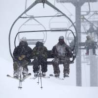 Skiers ride up a chair lift as snow falls on Mammoth Mountain in California Monday in this handout photo provided by Mammoth Mountain Ski Area.   REUTERS/KEVIN WESTENBARGER / MAMMOTH MOUNTAIN SKI AREA / HANDOUT VIA REUTERS