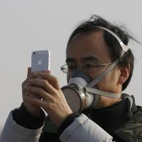 A man wearing a mask takes a picture with his smartphone in Beijing's Tiananmen Square amid heavy pollution Sunday. | REUTERS