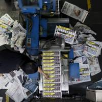 An employee takes a copy of the Apple Daily newspaper, published by Next Media Ltd., at the company's printing facility in Hong Kong on Thursday. The pro-democracy Apple Daily, which says it is hacked on an almost weekly basis, has tightened its email security software, and has its lawyers use couriers rather than email. | REUTERS