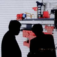 Visitors view machinery on a screen during the China Coal & Mining Expo in Beijing on Friday.   AP