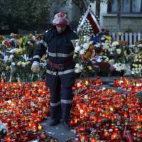 A fireman carries flowers as he walks between lit candles as thousands mourn the victims of a nightclub fire in Bucharest Sunday. Two young Romanian women died of severe burns in a hospital on Sunday after having been rescued from the fire at a Bucharest nightclub on Friday, doctors said, raising the death toll to 29. | OCTAV GANEA / INQUAM PHOTOS / REUTERS