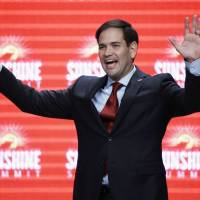 Republican presidential candidate Sen. Marco Rubio waves to the audience Friday at the conclusion of his remarks at the Sunshine Summit in Orlando, Florida. Out on the presidential campaign trail, Rubio and Ted Cruz are rising in the polls. | AP