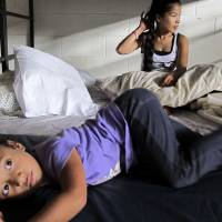 Keioleen Helly, 3, and her aunt, Kifency Kinny, 24, lay on a bed Oct. 9 in the Institute for Human Services family shelter in Honolulu. Kifency's mother, Kionina Kaneso, arrived in 2004 and worked odd jobs as a dishwasher and assembly line worker to pay for her son's flight to Hawaii so he could get medical treatment for a heart condition. | AP