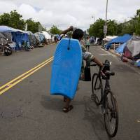 A homeless construction worker carries his bodyboard through an encampment in Honolulu's Kakaako district on Aug. 24. | AP
