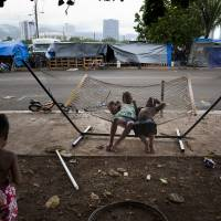 Two children play on a hammock at a homeless encampment in the Kakaako district of Honolulu on Aug. 25. Micronesians make up about a third of people living here. | AP