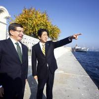 Prime Minister Shinzo Abe and his Turkish counterpart, Ahmet Davutoglu, speak as they stand on the Bosporus in Istanbul on Saturday ahead of the two-day Group of 20 summit. | AP