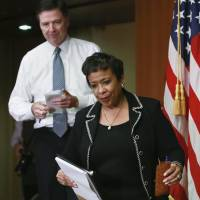 U.S. Attorney General Loretta Lynch and FBI Director James Comey arrive at a media briefing at the Justice Department in Washington Thursday. | REUTERS