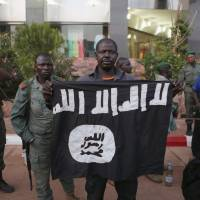 Malian security officials show a jihadist flag they said belonged to attackers in front of the Radisson hotel in Bamako, Mali, on Friday. | REUTERS