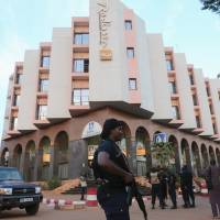 A Malian police officer stands guard in front of the Radisson hotel in Bamako, Mali, on Friday. | REUTERS