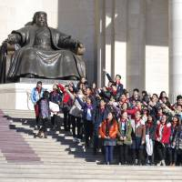 Schoolchildren pose for a photo near the statue of Genghis Khan standing in Sukhbaatar Square in Ulan Bator, the Mongolian capital, on Friday. | AP