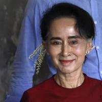 Democracy leader Aung San Suu Kyi smiles to supporters as she visits a polling station in her constituency of Kawhmu Township in Myanmar on Sunday.   REUTERS