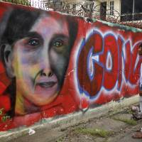 A man looks at a graffiti congratulating Myanmar's opposition leader Aung San Suu Kyi and her party's election victory in Mandalay, Myanmar, Wednesday Nov. 11, 2015. Suu Kyi has won her parliamentary seat, official results showed Wednesday, leading a near total sweep by her party that will give the country its first government in decades that isn't under the military's sway. | AP