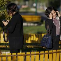 Young women chat in a park in front of Pothonggang Department Store in central Pyongyang on Oct. 11.   REUTERS