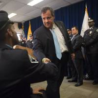 New Jersey Gov. Chris Christie greets Camden County Police Officer Tyrrell Bagby after addressing the Camden County Police Force on the sweeping public safety reforms and the progress made together with the City of Camden to bring down crime, Monday. | JOHN ZIOMEK / CAMDEN COURIER-POST VIA AP