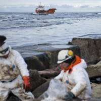 Clean-up workers shovel oil into bags on Russia's Sakhalin Island on Sunday. The tanker is seen to the rear. | REUTERS