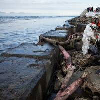 Workers scrape crude oil from the shore in a clean-up effort involving several Russian agencies. The tanker continues to lie on rocks about 150 meters offshore. | AP