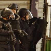French special police secure the area as shots are exchanged in Saint Denis, a suburb of Paris, on Wednesday during an operation to catch suspects in Friday night's deadly attacks in the French capital. | REUTERS