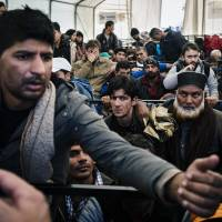 A man argues as he waits along with other migrants and refugees at a registration camp after crossing the Greek-Macedonian border near Gevgelija on Saturday. French authorities said a Syrian passport found near one of the Paris attack gunmen was for a man who arrived in Greece last month among purported refugees. | AFP-JIJI