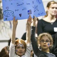 Girls hold up a sign on Friday during a rally at Unitarian Universalist Church in Roanoke, Virginia, after Mayor David Bowers invoked the mass detention of Japanese-Americans during World War II in comments about keeping Syrian refugees out of the region. | AP