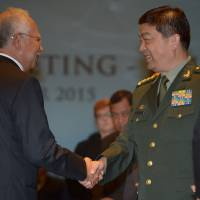 Malaysian Prime Minister Najib Razak (left) shakes hands with Chinese Defense Minister Chang Wanquan during an Association of Southeast Asian Nations defense ministerial meeting in Subang, on the outskirts of Kuala Lumpur, on Wednesday. | AFP-JIJI