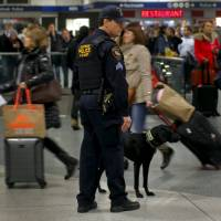 An Amtrak Police K-9 team patrols a busy Pennsylvania Station in the Manhattan borough of New York City Wednesday, one day ahead of the Thanksgiving holiday. Millions of Americans embark on their annual Thanksgiving travels on Wednesday, one of the busiest travel days of the year.   REUTERS