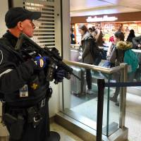 An Amtrak Police officer watches passengers as they board a train at Penn Station on Wednesday in New York.   AFP-JIJI