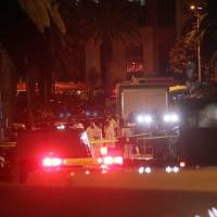 Tunisian police and forensics gather at the site of a bomb blast on a bus (right) transporting Tunisia's presidential guard in central Tunis on Tuesday. | AFP-JIJI