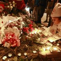 A Tunisian girl places flowers during a candle vigil on Wednesday at the site of the attack on a bus in central Tunis that killed several presidential guards the previous day. | AFP-JIJI