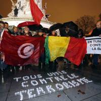 People hold a Tunisian and a Malian flag as they stand behind candles forming the words 'All united against terrorism' on the Place de la Republique in Paris on Wednesday during a gathering to commemorate the victims of recent attacks in Tunis, Bamako and Paris. | AFP-JIJI