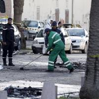 A sanitary service worker cleans the scene of a suicide bomb attack in Tunis Wednesday. | REUTERS