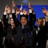 Prime Minister Shinzo Abe holds a banzai cheer with members of his Liberal Democratic Party in Tokyo on Sunday during a ceremony marking the party's 60th anniversary.   REUTERS
