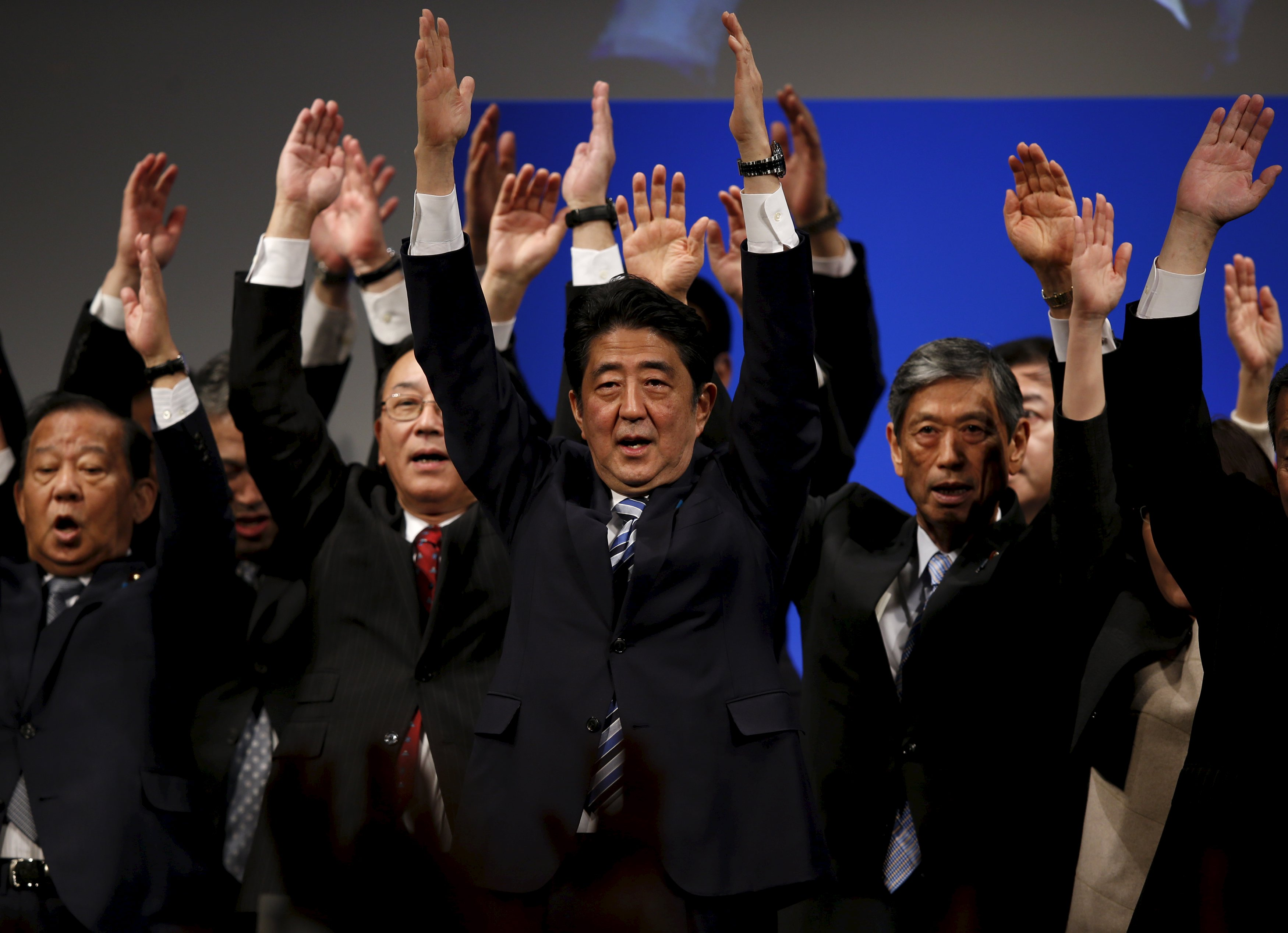 Prime Minister Shinzo Abe holds a banzai cheer with members of his Liberal Democratic Party in Tokyo on Sunday during a ceremony marking the party's 60th anniversary. | REUTERS