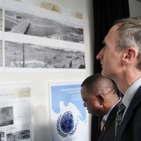 Diplomats at the U.N.'s office in Vienna on Tuesday look at photographs showing parts of the cities of Hiroshima and Nagasaki shortly after the 1945 atomic bombings. The pictures are now on permanent display. | KYODO