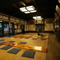 A worker prepares the dining room of Komakata Dozeu for another day of business. | RIE ISHII