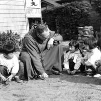 The Rev. Charles Brozat addresses children at play in this undated photograph. The former U.S. serviceman, decorated in the Pacific War, returned to Japan as a missionary and served there for 54 years.   SOCIETY OF ATONEMENT