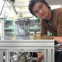Tomohiro Nishitani, co-founder of Nagoya-based technology startup Photo Electron Soul, poses with its electron beam device. | PHOTO ELECTRON SOUL / CHUNICHI SHIMBUN