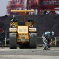 Workers repair a coal loading facility at Onahama port in Iwaki, Fukushima Prefecture. Japan's government and industry are backing emerging coal technologies that they say are less damaging to the environment. | BLOOMBERG