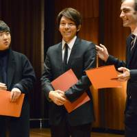 Shoichi Yabuta (center) is awarded first prize for composition at the 2015 Geneva International Music Competition in Geneva on Sunday. | KYODO